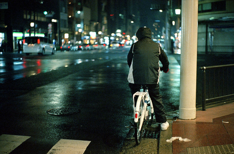 Rear view of man sitting on bicycle at road in city during night