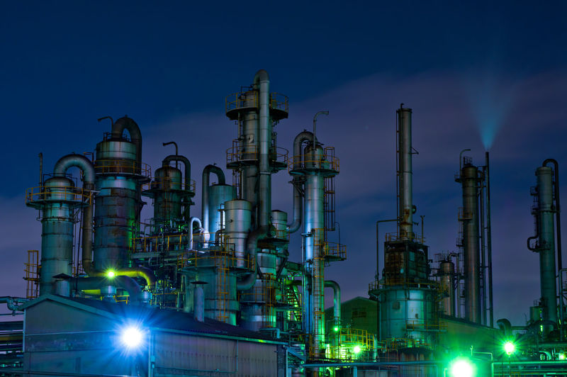Low angle view of illuminated factory against sky at night