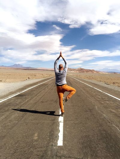 Rear View Of Mid Adult Man Practicing Tree Pose On Road Against Sky