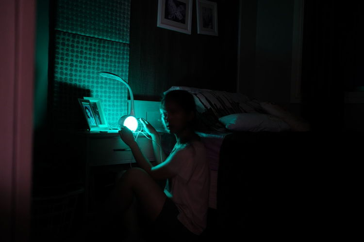 Side view of woman holding illuminated light on night table