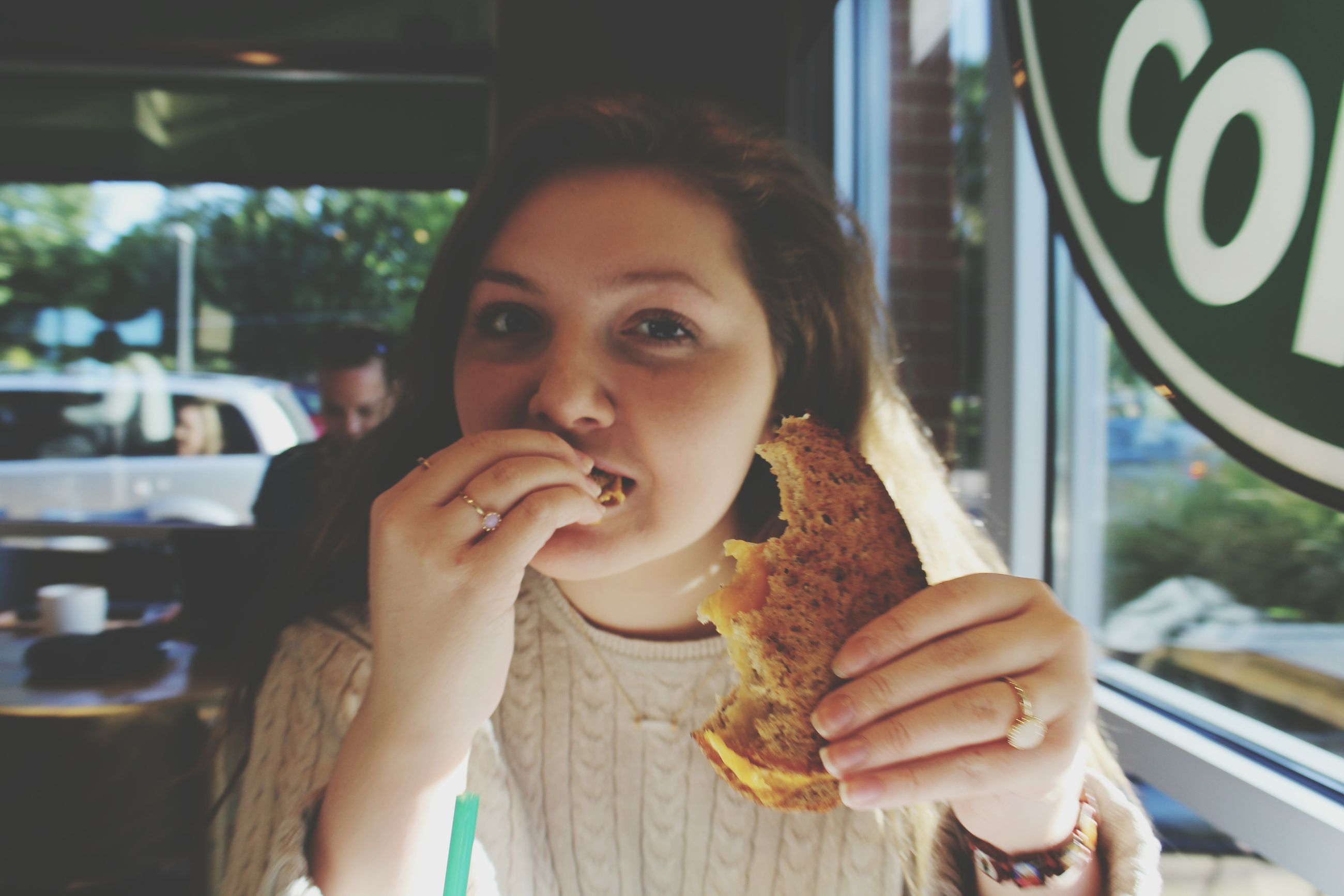 person, lifestyles, focus on foreground, food and drink, indoors, holding, leisure activity, headshot, looking at camera, portrait, smiling, food, childhood, waist up, close-up, front view, casual clothing, head and shoulders