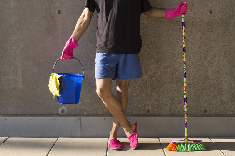 Low Section Of Man With Cleaning Equipment Standing Against Wall