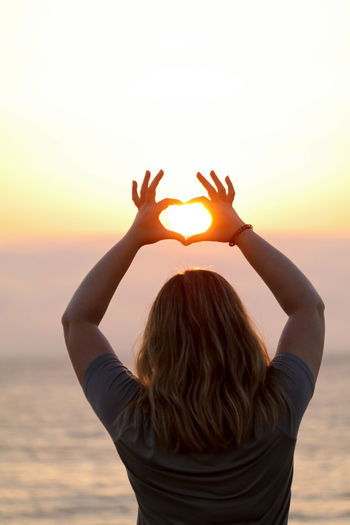Rear view of woman making heart shape with sun in between