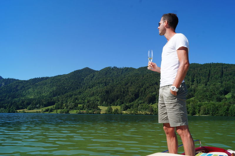 Man With Champagne Flute Standing On Boat By Tree Mountains Against Clear Blue Sky