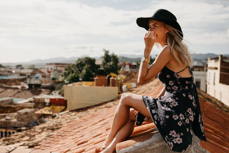 Side View Of Smiling Young Woman Sitting On Rooftop