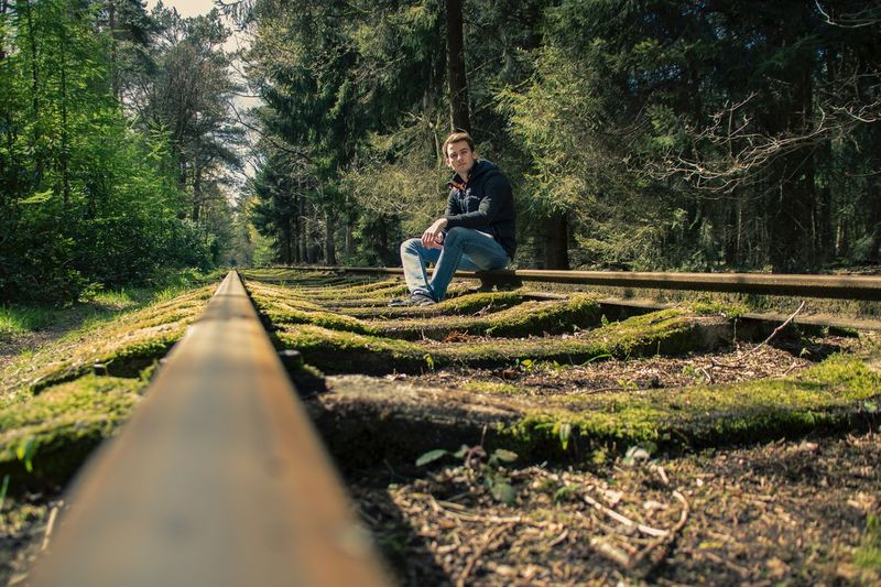 Low angle portrait of man sitting on abandoned railroad track