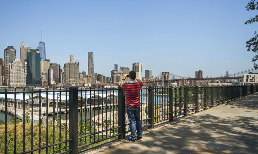 Rear view of man standing on railing in city
