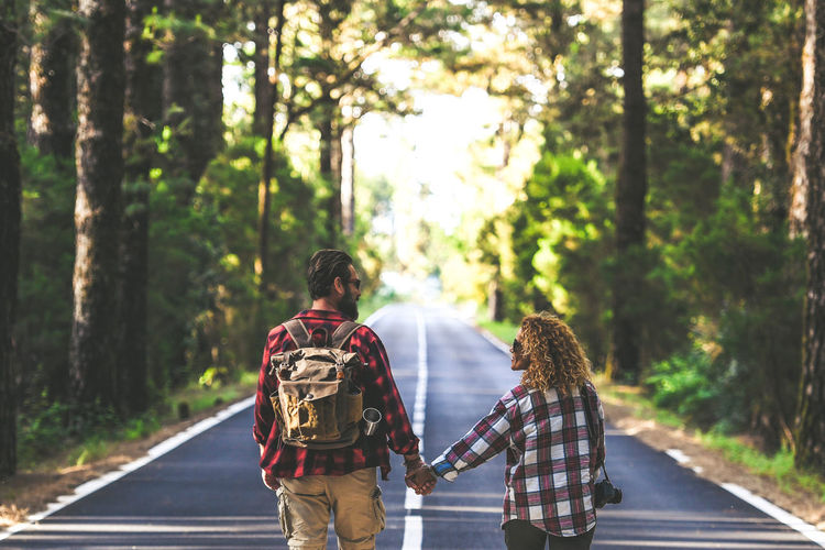 Rear view of couple walking on road amidst trees