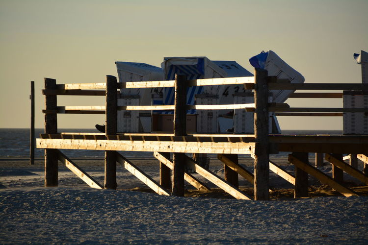 Hooded Chairs On Pier At Beach Against Sky