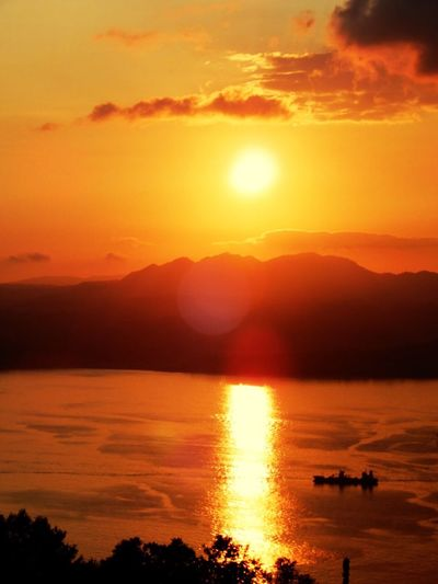 Sunset Orange Color Sun Beauty In Nature Scenics Nature Water Sky Tranquil Scene Reflection Silhouette Mountain Sunlight Dramatic Sky Tranquility Idyllic Outdoors Sea Cloud - Sky No People