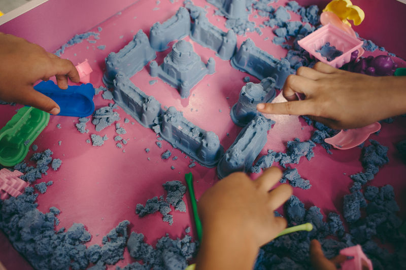 Cropped hands of children making castle from clay