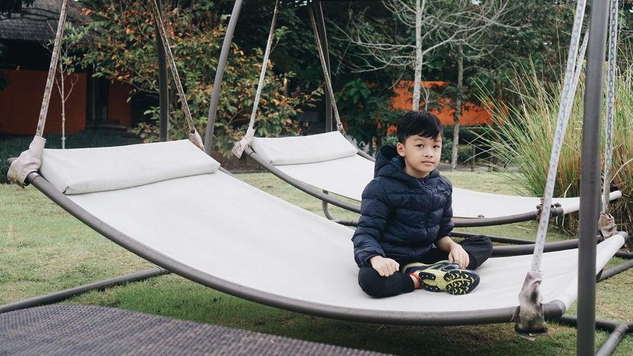 Portrait of boy sitting on hammock