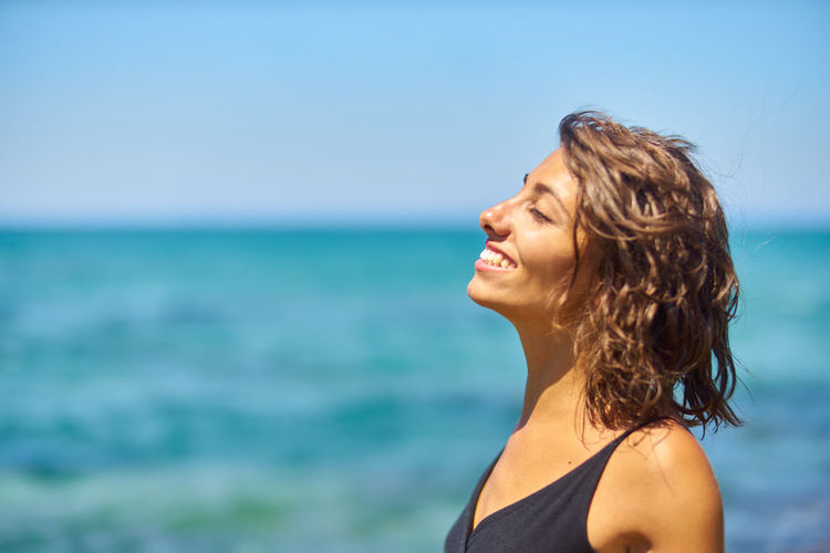 Close-Up Of Smiling Young Woman Against Sea