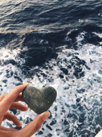 Midsection of person holding rock in sea
