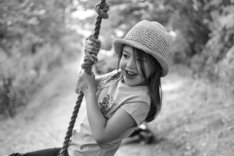 Cheerful girl swinging on rope at park