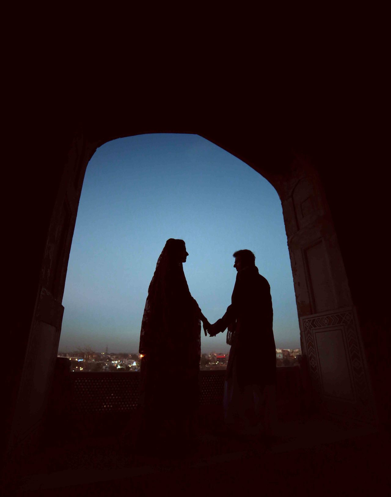 Rear view of silhouette couple holding hands against clear blue sky