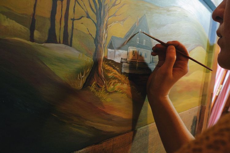 Cropped Image Of Woman Drawing On Canvas In Cottage