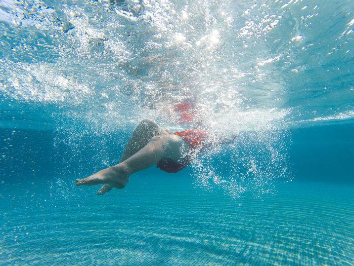 Girl swimming underwater in swimming pool