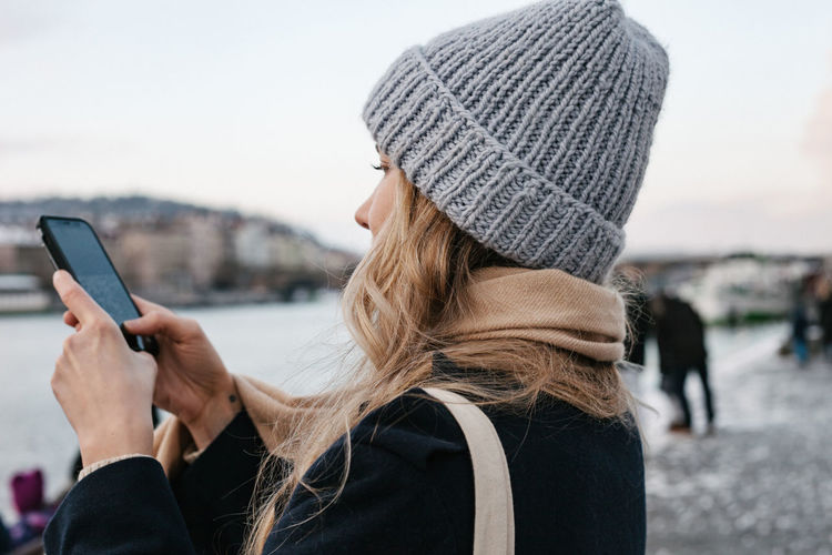 Portrait of woman holding mobile phone in winter