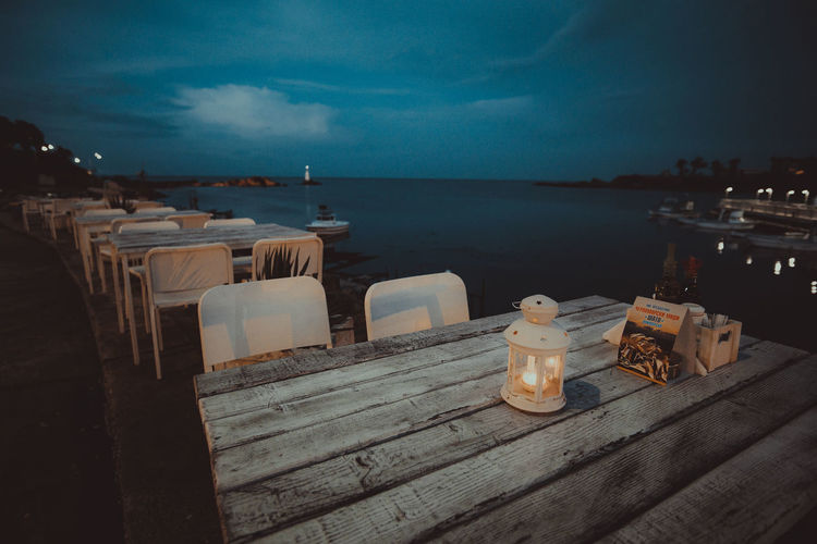 Empty tables and chairs by sea at dusk