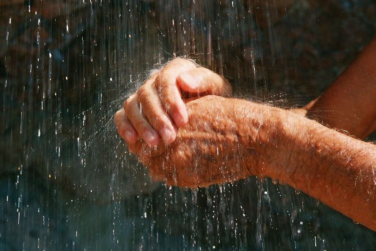 Close-Up Of A Person Hands In Outdoor Shower