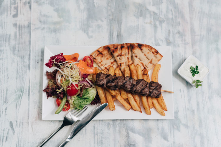 Greek souvlaki meal Beef Cuisine Fork Greek Knife Meal Salad Skewer Souvlaki Beef Souvlaki Food French Fries Greek Food Pita Bread Plate Portion Souvlakia Suvlaki Table Tzatziki