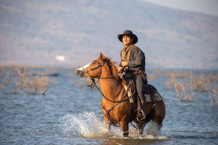 Man riding horse in sea