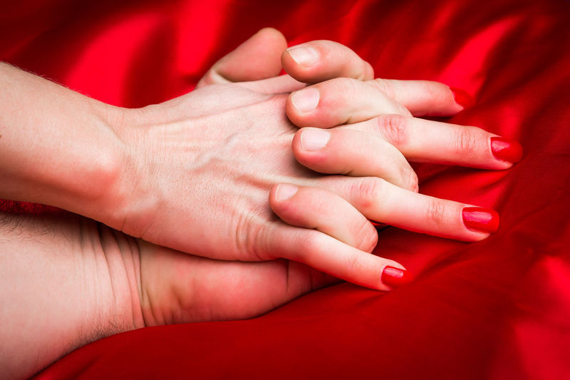 Cropped image of couple holding hands on bed