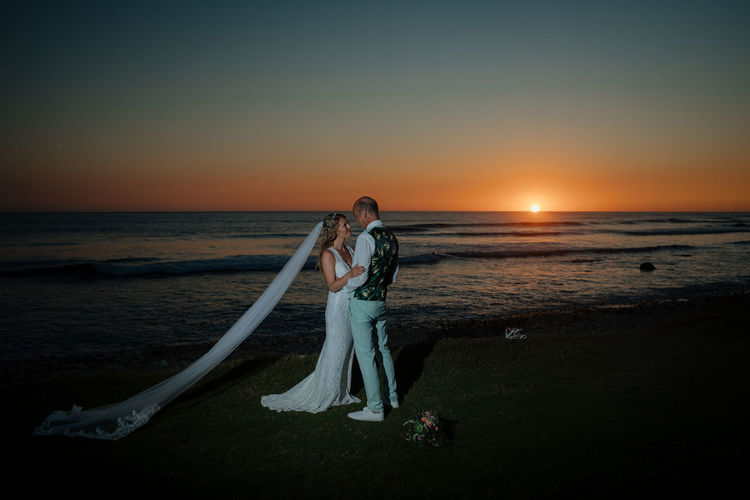Wedding couple standing on beach against sky during sunset