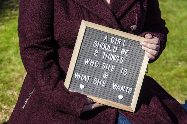 Midsection of woman holding slate with text outdoors