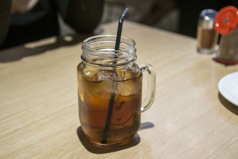 High angle view of ice tea with lemon in glass on wooden table