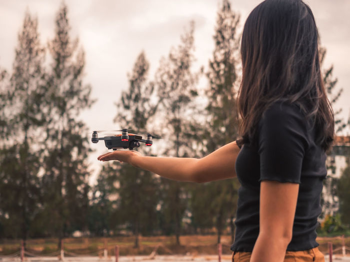 Asian young woman controlling flying drone against enjoying the weekend Drone  Photography Flying Control Technology Intelligent Landing TakeOff Pilot Aircraft Woman Enjoy Fun GPS Flight Motion Outdoors Smart Wifi Command Controlling Sky Sunny Vintage One Person