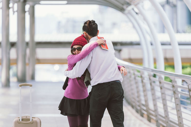 Smiling Woman Embracing Boyfriend On Elevated Walkway At Airport