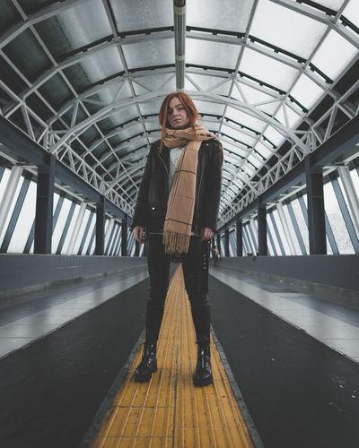 Portrait of young woman standing on footbridge