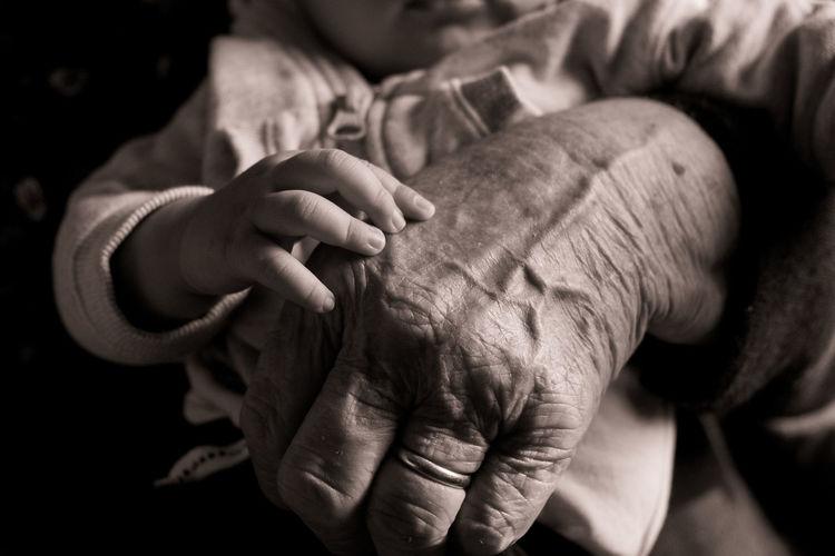 Close-up of grandparent carrying grandchild