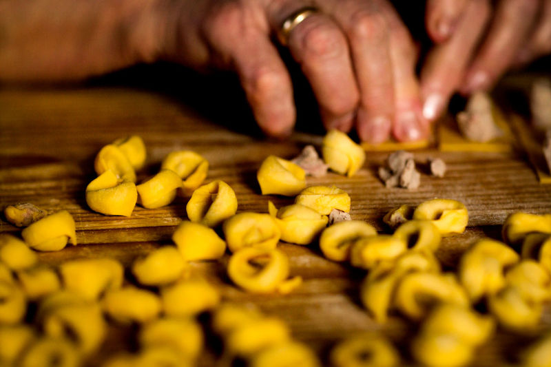 Tortellini Modena Close-up Finger Food Food And Drink Freshness Hand Holding Human Body Part Human Hand Indoors  Italian Food Men One Person Parma Ham Parmigiano Pasta Preparation  Preparing Food Real People Selective Focus Table Tortellini  Wood - Material Working