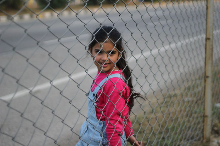 Portrait of girl standing by chainlink fence