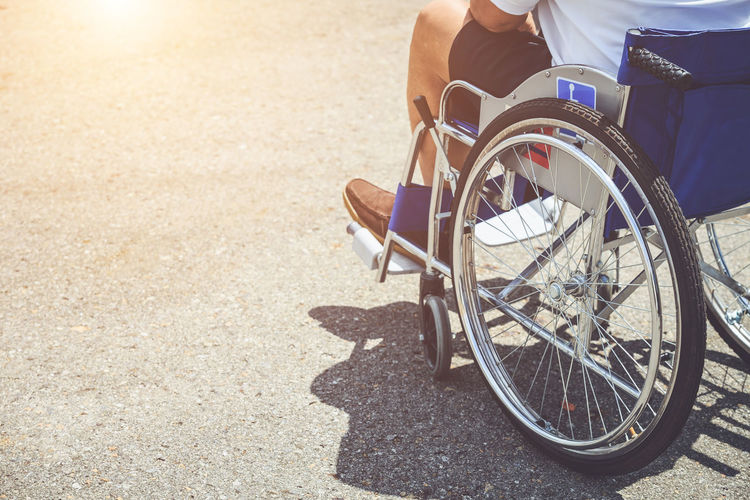 Low section of man sitting on wheelchair at road