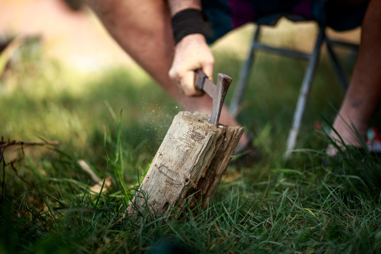 Low section of man cutting wood on field
