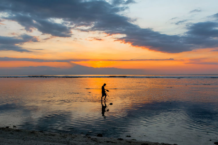 Silhouette of person walking on beach at sunset