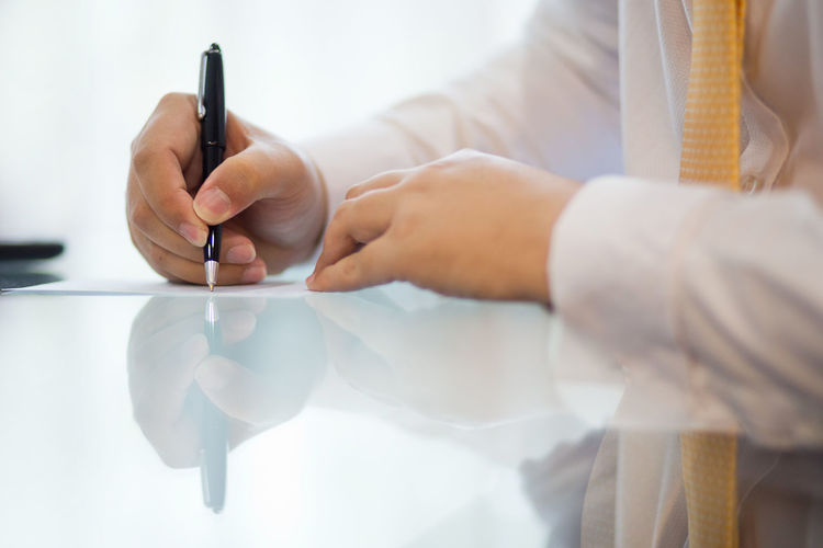 Male hand taking notes during meeting Human Hand Holding Hand One Person Indoors  Human Body Part Adult Pen Business Person Office Writing Midsection Corporate Business Business Communication Table Occupation Close-up Paperwork Meeting