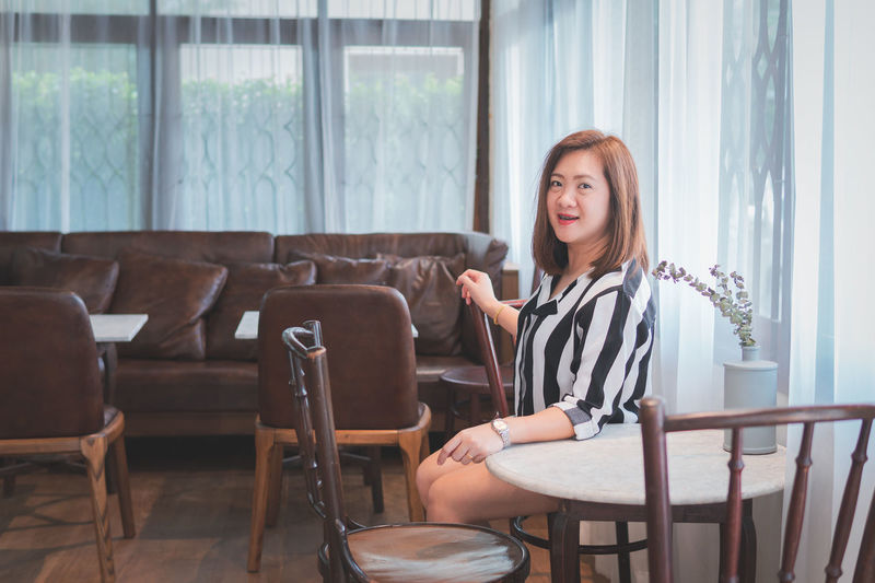 Smiling Woman Sitting On Chair In Restaurant