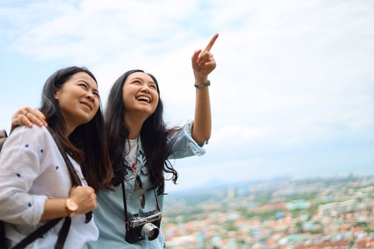 Young Adult Young Women Two People Standing Togetherness Sky Emotion Gesturing Waist Up Lifestyles Adult Nature City Happiness Women Bonding Real People Leisure Activity Casual Clothing Friendship Positive Emotion Outdoors Human Arm Cityscape Arms Raised