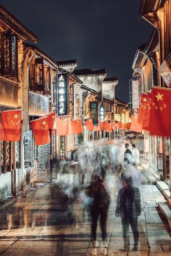 People walking on street against buildings in city at night
