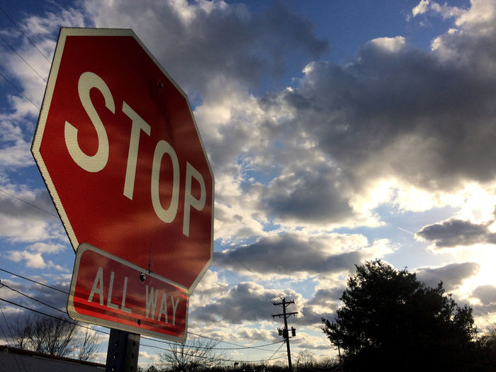 stop time and let the world move on. the sun sets but you can not halt night. All Way Blue Cloud Cloudy Communication Dusk Information Sign Low Angle View Octagonal Overcast Red Reflection Road Sign Sign Silhouette Sky Stop Sunlight Sunset Text Warning Sign Weather White