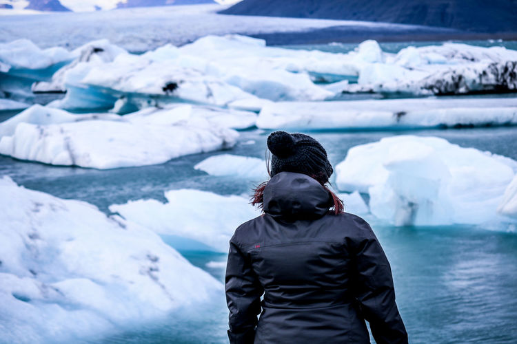 Rear view of man standing in frozen river