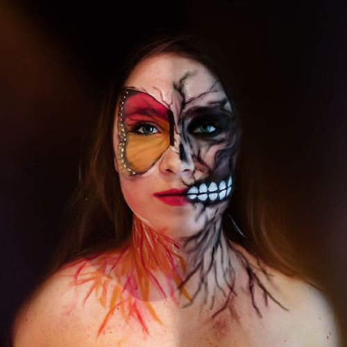 Close-Up Portrait Of Woman With Butterfly And Devil Face Paint