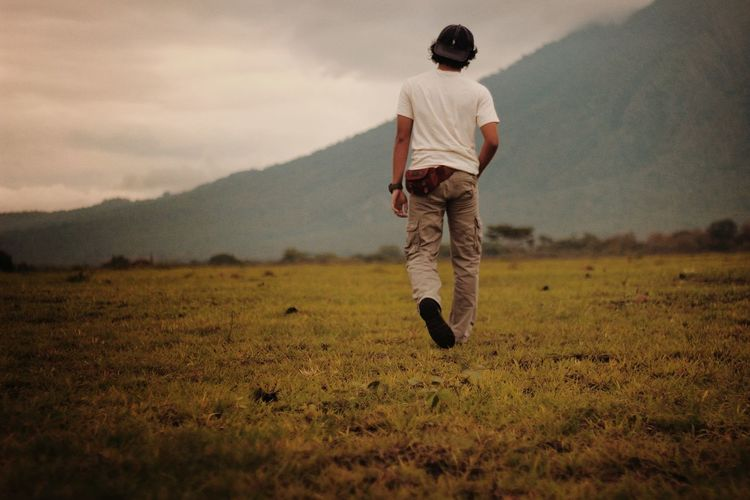 Rear view of man walking on field against sky
