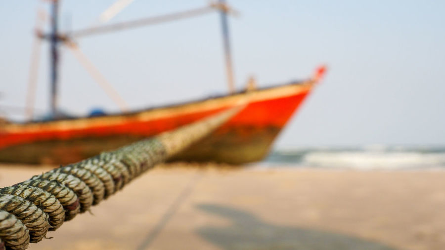 Close-up of fishing boat on beach against clear sky