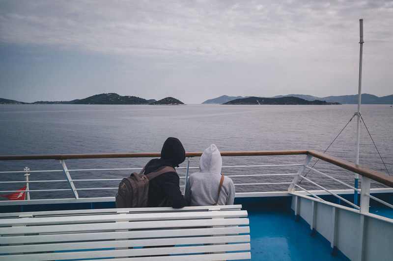 Bonding Casual Clothing Full Length Leisure Activity Lifestyles Looking At View Men Nikos Pandazaras Person Pier Railing Rear View Sea Sitting Sky Standing Togetherness Water
